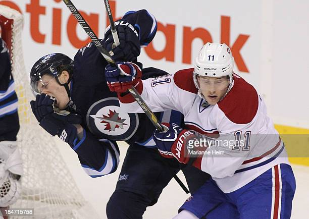 Jacob Trouba of the Winnipeg Jets gets hit in the face colliding with Brendan Gallagher of the Montreal Canadiens in first period action of an NHL...