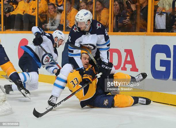 Jacob Trouba of the Winnipeg Jets holds down Viktor Arvidsson of the Nashville Predators during the first period in Game Two of the Western...
