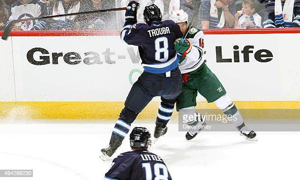 Jacob Trouba of the Winnipeg Jets lays the body into Jason Zucker of the Minnesota Wild during second period action at the MTS Centre on October 25...