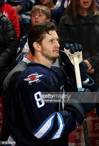 Jacob Trouba of the Winnipeg Jets looks on from the bench during the singing of the National anthems prior to puck drop against the Los Angeles Kings...