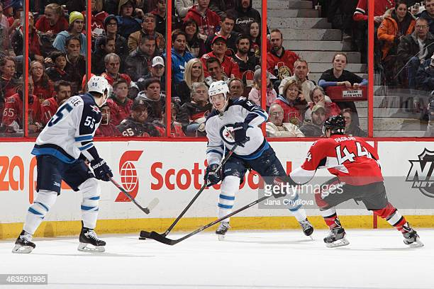 Jacob Trouba of the Winnipeg Jets passes the puck against JeanGabriel Pageau of the Ottawa Senators during an NHL game at Canadian Tire Centre on...