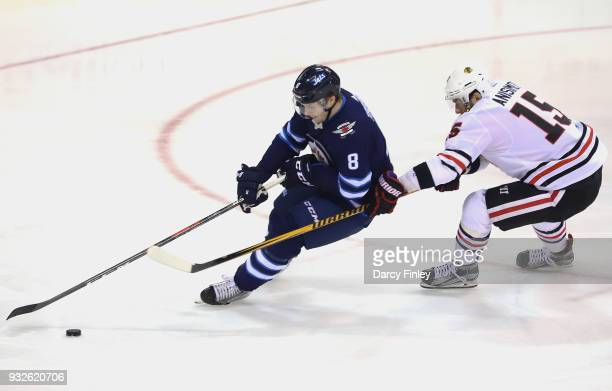 Jacob Trouba of the Winnipeg Jets plays the puck away from Artem Anisimov off the Chicago Blackhawks during second period action at the Bell MTS...