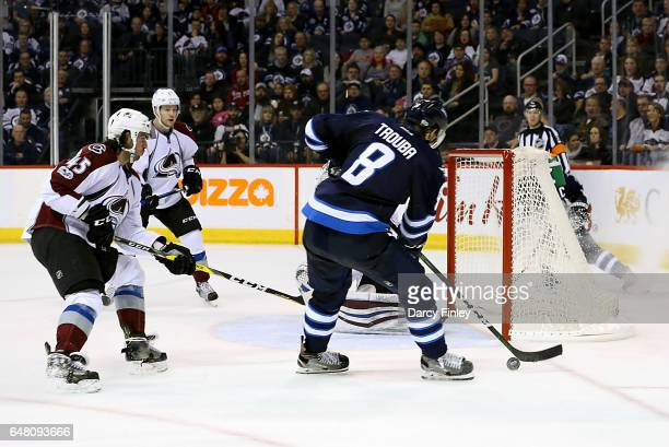 Jacob Trouba of the Winnipeg Jets plays the puck beside the net as Mark Barberio of the Colorado Avalanche gives chase during third period action at...