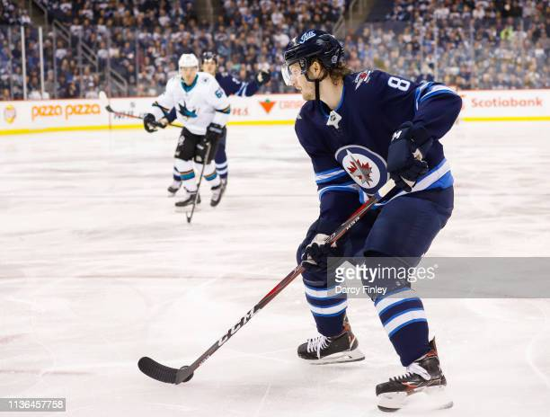 Jacob Trouba of the Winnipeg Jets plays the puck down the ice during second period action against the San Jose Sharks at the Bell MTS Place on March...