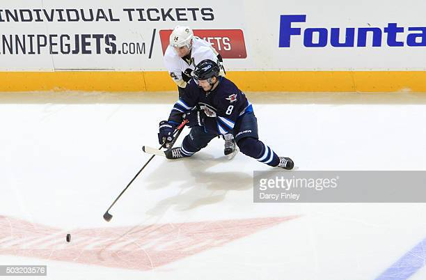 Jacob Trouba of the Winnipeg Jets pokes the puck away as he defends against Chris Kunitz of the Pittsburgh Penguins during third period action at the...