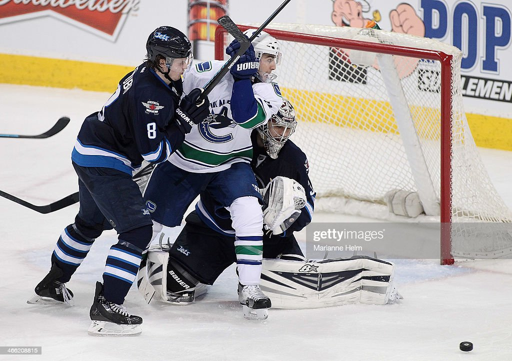 Jacob Trouba #8 of the Winnipeg Jets puts pressure on Alexandre Burrows #14 of the Vancouver Canucks in front of goaltender Ondrej Pavelec #31 in third period action in an NHL game at the MTS Centre on January 31, 2014 in Winnipeg, Manitoba, Canada.