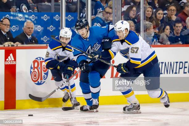 Jacob Trouba of the Winnipeg Jets rushes between Zach Sanford and David Perron of the St Louis Blues as they follow the loose puck during second...