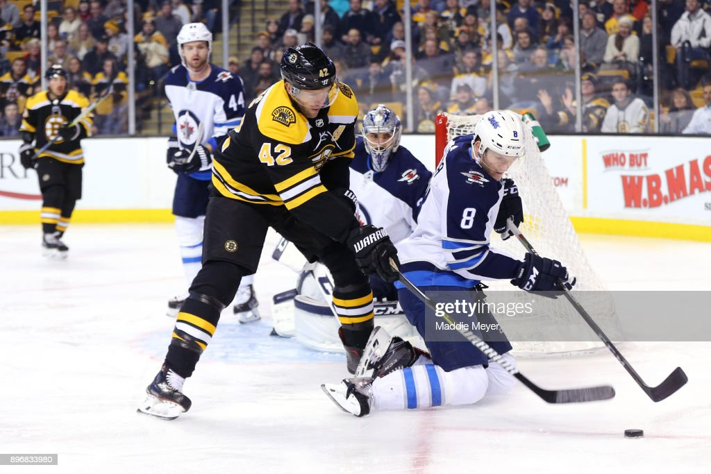 Jacob Trouba #8 of the Winnipeg Jets shields the puck from David Backes #42 of the Boston Bruins during the first period at TD Garden on December 21, 2017 in Boston, Massachusetts.