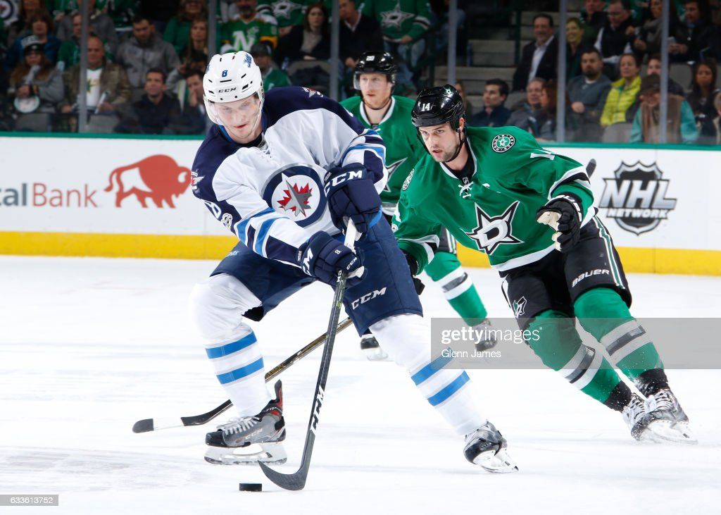 Jacob Trouba #8 of the Winnipeg Jets tries to keep the puck away against Jamie Benn #14 of the Dallas Stars at the American Airlines Center on February 2, 2017 in Dallas, Texas.