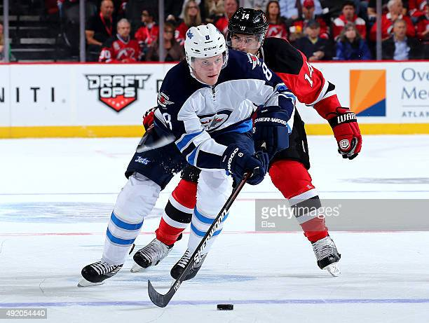 Jacob Trouba of the Winnipeg Jets tries to keep the puck from Adam Henrique of the New Jersey Devils in the first period on October 9 2015 at the...
