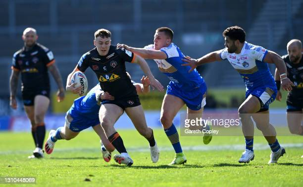Jacob Trueman of Castleford is tackled by Alex Mellor of Leeds during the Betfred Super League match between Leeds Rhinos and Castleford Tigers at...