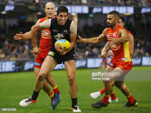 Jacob Weitering of the Blues handballs from Gary Ablett of the Suns and Adam Saad of the Suns during the round four AFL match between the Carlton...