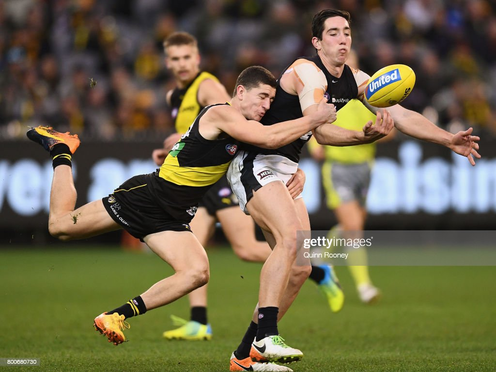 Jacob Weitering of the Blues handballs whilst being tackled by Jason Castagna of the Tigers during the round 14 AFL match between the Richmond Tigers and the Carlton Blues at Melbourne Cricket Ground on June 25, 2017 in Melbourne, Australia.