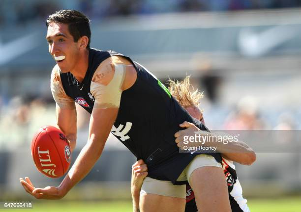 Jacob Weitering of the Blues handballs whilst being tackled by Jimmy Webster of the Saints during the 2017 JLT Community Series AFL match between the...