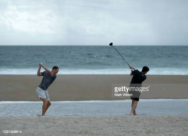 Jacob Whitehead and Matt Jones hit golf balls into the surf as Hurricane Florence approaches, on September 11, 2018 in Wrightsville Beach, United...