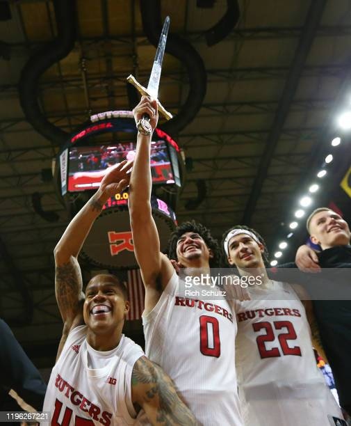 Jacob Young, Geo Baker and Caleb McConnell of the Rutgers Scarlet Knights celebrate their 75-72 victory over the Nebraska Cornhuskers during a...