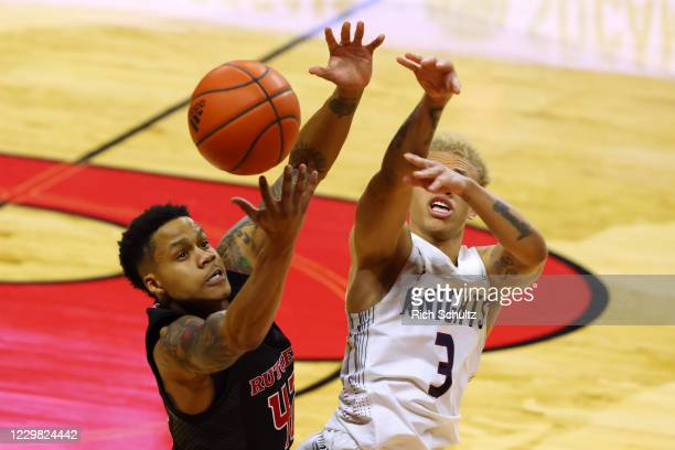 Jacob Young of the Rutgers Scarlet Knights battles Jahlil Jenkins of the Fairleigh Dickinson Knights during the first half of an NCAA college...