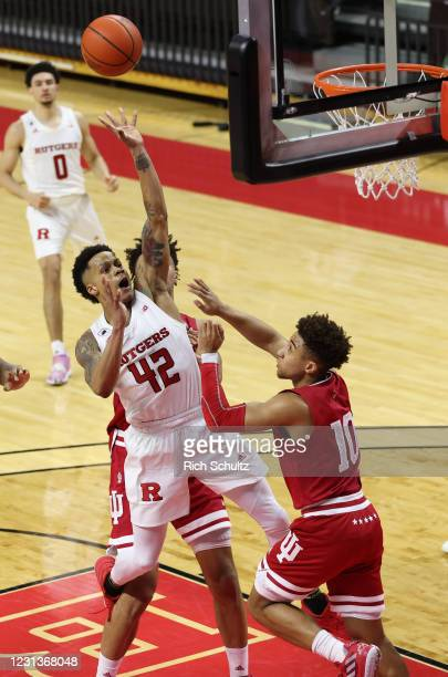 Jacob Young of the Rutgers Scarlet Knights shoots against Trayce Jackson-Davis and Rob Phinisee of the Indiana Hoosiers during the second half of an...