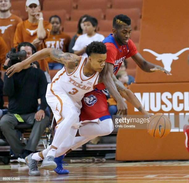 Jacob Young of the Texas Longhorns and Exavian Christon of the Louisiana Tech Bulldogs fight for a loose ball at the Frank Erwin Center on December...