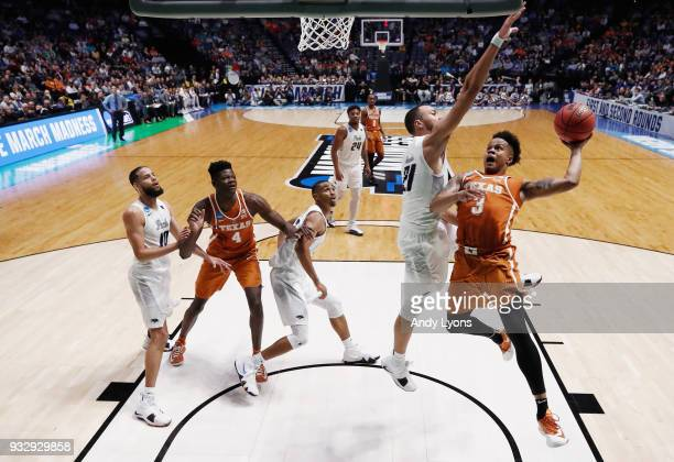 Jacob Young of the Texas Longhorns goes up for a layup defended by Kendall Stephens of the Nevada Wolf Pack during the game in the first round of the...
