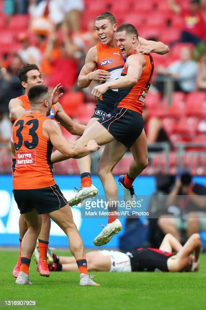 JacobHopper of the Giants celebrates kicking the winning goal with his teammates during the round eight AFL match between the Greater Western Sydney...