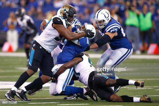 Jacoby Brissett of the Indianapolis Colts is hit by Calais Campbell of the Jacksonville Jaguars after throwing a pass during the first half at Lucas...