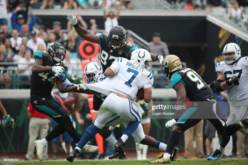 Jacoby Brissett #7 of the Indianapolis Colts is pressured by a group of Jacksonville Jaguars defenders in the second half of their game at EverBank Field on December 3, 2017 in Jacksonville, Florida.