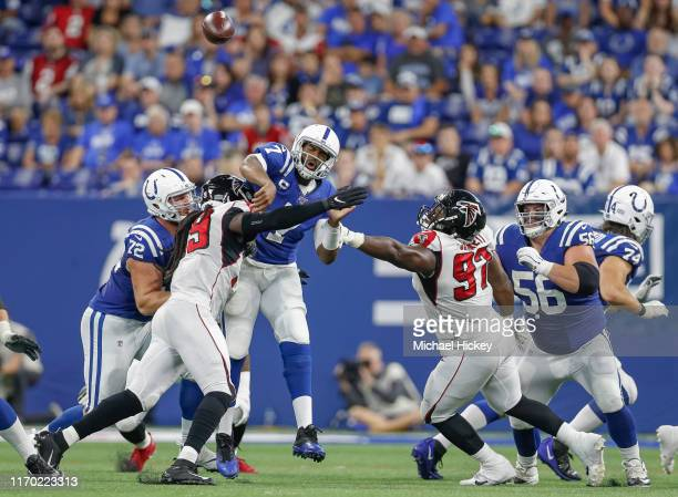 Jacoby Brissett of the Indianapolis Colts passes the ball under pressure from Adrian Clayborn and Grady Jarrett of the Atlanta Falcons at Lucas Oil...