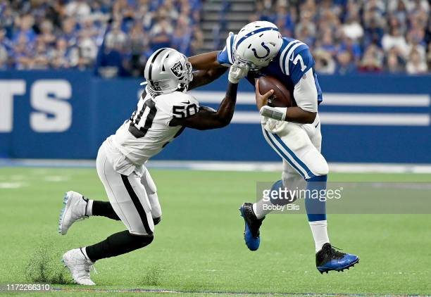 Jacoby Brissett of the Indianapolis Colts stiff arms Nicholas Morrow of the Oakland Raiders as he is tackled by his facemask in the fourth quarter of...