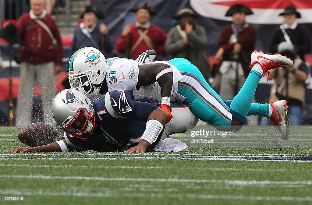 Jacoby Brissett #7 of the New England Patriots fumbles the ball as he is sacked by Michael Thomas #31 of the Miami Dolphins during the second half at Gillette Stadium on September 18, 2016 in Foxboro, Massachusetts.