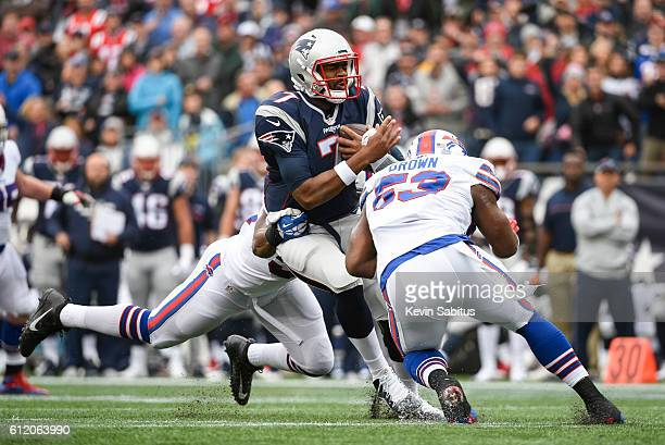 Jacoby Brissett of the New England Patriots is wrapped up by Jerry Hughes and Zach Brown of the Buffalo Bills in the second quarter at Gillette...