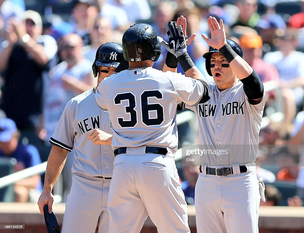 Jacoby Ellsbury #22 and Brett Gardner #11 of the New York Yankees celebrate with Carlos Beltran #36 after Beltran drove them all in with a home run in the first inning against the New York Mets during interleague play on September 19, 2015 at Citi Field in the Flushing neighborhood of the Queens borough of New York City.