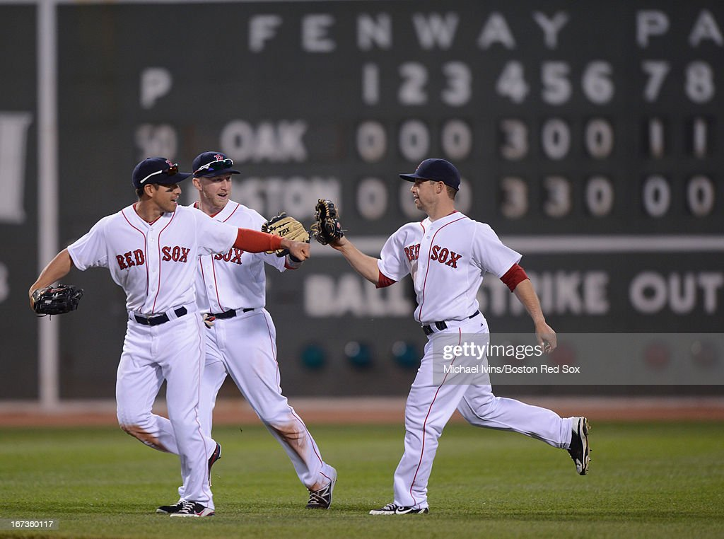 Jacoby Ellsbury #2, Mike Carp #37 and Daniel Nava #29 of the Boston Red Sox celebrate a 6- win against the Oakland Athletics on April 24, 2013 at Fenway Park in Boston, Massachusetts.