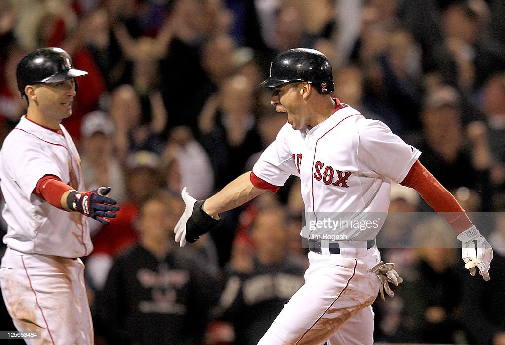 Jacoby Ellsbury #2 of the Boston Red Sox celebrates an inside the park home with Marco Scutaro #10 of the Boston Red Sox during a game against the Baltimore Orioles during the second game of a doubleheader at Fenway Park September 19, 2011 in Boston, Massachusetts.
