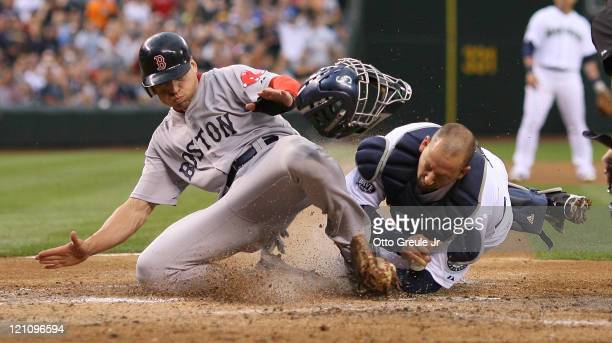 Jacoby Ellsbury of the Boston Red Sox is tagged out by catcher Josh Bard of the Seattle Mariners on a fly ball to right field by Dustin Pedroia at...