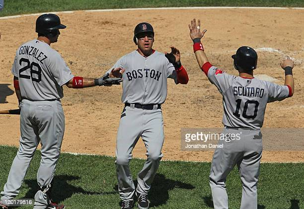 Jacoby Ellsbury of the Boston Red Sox is welcomed by teammates Adrian Gonzalez and Marco Scutaro after scoring in the 7th inning against the Chicago...