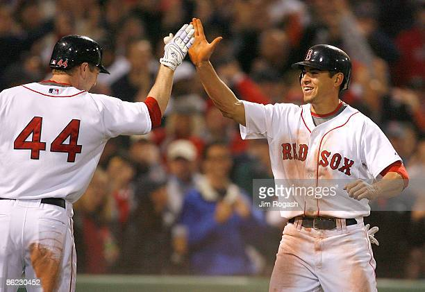 Jacoby Ellsbury of the Boston Red Sox steals home and celebrates with teammate Jason Bay against the New York Yankees at Fenway Park April 26 2009 in...