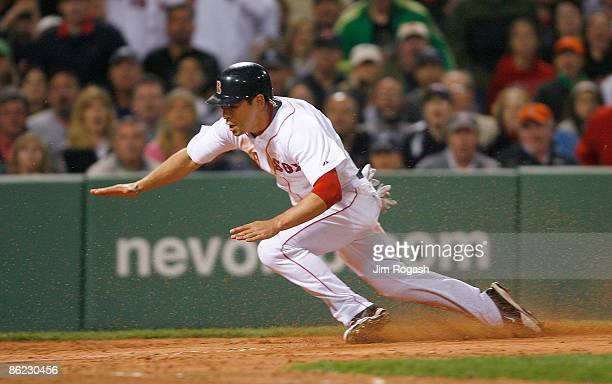 Jacoby Ellsbury of the Boston Red Sox steals home by Jorge Posada of the New York Yankees at Fenway Park April 26 2009 in Boston Massachusetts