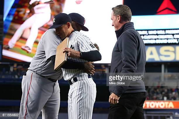 Jacoby Ellsbury of the New York Yankees and David Cone presents a gift to David Ortiz of the Boston Red Sox during a pregame ceremony at Yankee...