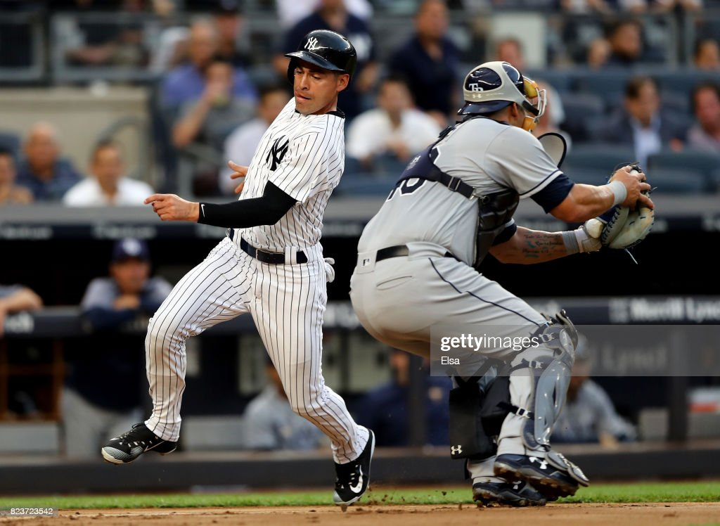 Jacoby Ellsbury #22 of the New York Yankees beats the tag and scores past Wilson Ramos #40 of the Tampa Bay Rays in the second inning on July 27, 2017 at Yankee Stadium in the Bronx borough of New York City.
