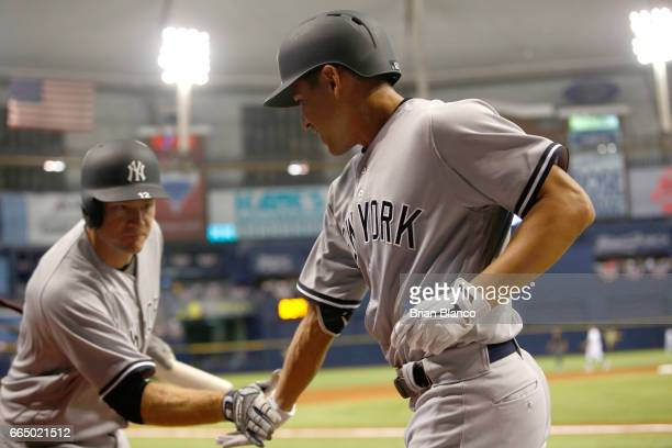 Jacoby Ellsbury of the New York Yankees celebrates his home run with Chase Headley during the second inning of a game against the Tampa Bay Rays on...