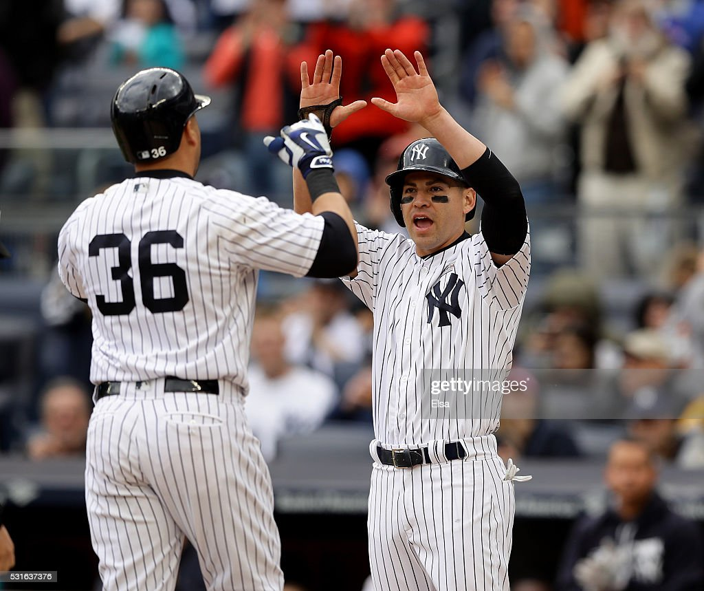 Jacoby Ellsbury #22 of the New York Yankees congratulates teammate Carlos Beltran #36 after Beltran hit his 400th career home run in the seventh inning against the Chicago White Sox at Yankee Stadium on May 15, 2016 in the Bronx borough of New York City.