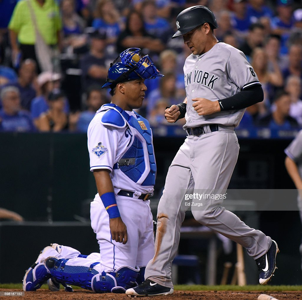Jacoby Ellsbury #22 of the New York Yankees crosses home past Salvador Perez #13 of the Kansas City Royals as he scores on a Didi Gregorius #18 sacrifice fly in the sixth inning at Kauffman Stadium on August 31, 2016 in Kansas City, Missouri.