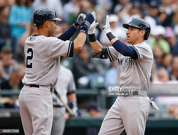 Jacoby Ellsbury of the New York Yankees is congratulated by Derek Jeter after hitting a tworun home run in the first inning against the Seattle...