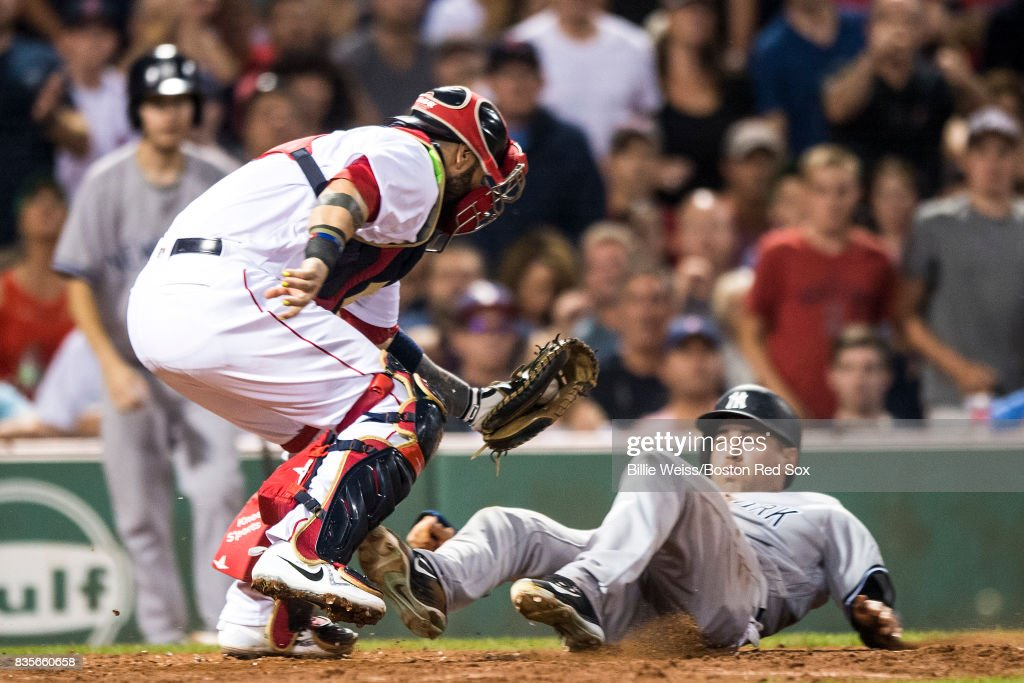 Jacoby Ellsbury #22 of the New York Yankees is tagged out at home plate by Sandy Leon #3 of the Boston Red Sox during the eighth inning of a game on August 19, 2017 at Fenway Park in Boston, Massachusetts.