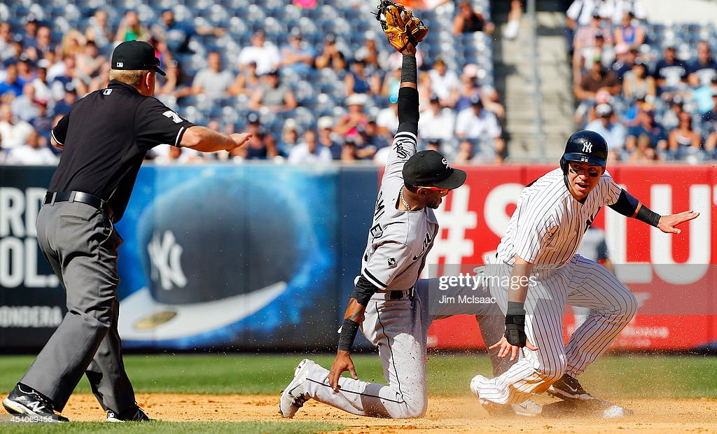Jacoby Ellsbury #22 of the New York Yankees steals second base in the ninth inning ahead of the tag from Alexei Ramirez #10 of the Chicago White Sox as umpire Mike Muchlinski makes the call at Yankee Stadium on August 24, 2014 in the Bronx borough of New York City.