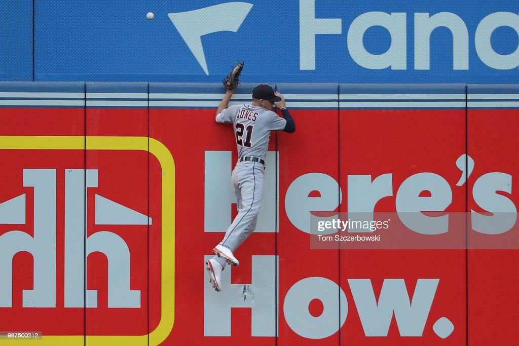JaCoby Jones #21 of the Detroit Tigers climbs the left field wall but cannot get to a two-run home run hit by Justin Smoak #14 of the Toronto Blue Jays in the fourth inning during MLB game action at Rogers Centre on June 29, 2018 in Toronto, Canada.