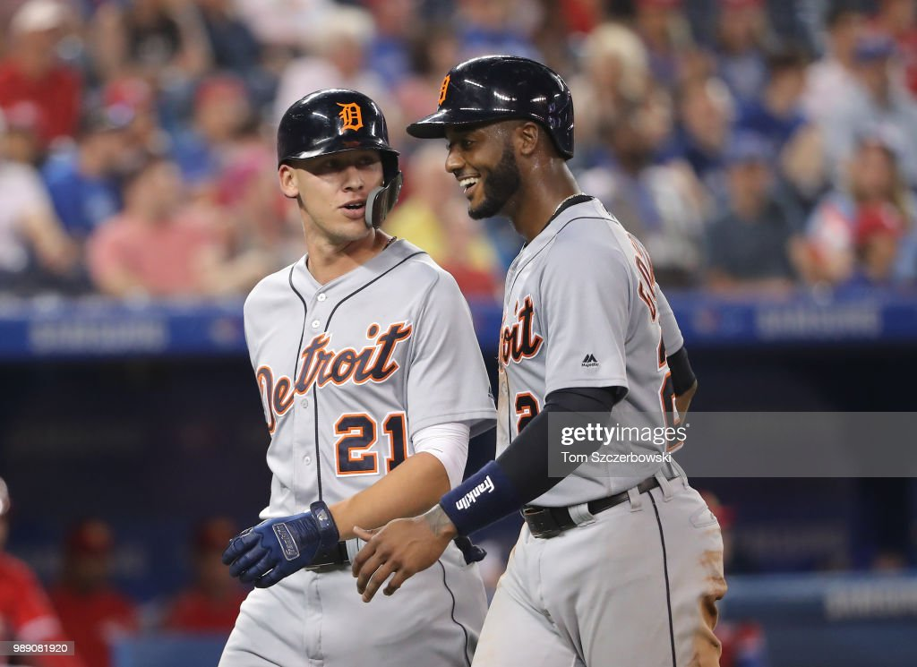 JaCoby Jones #21 of the Detroit Tigers is congratulated by Niko Goodrum #28 after hitting a two-run home run in the ninth inning during MLB game action against the Toronto Blue Jays at Rogers Centre on July 1, 2018 in Toronto, Canada.