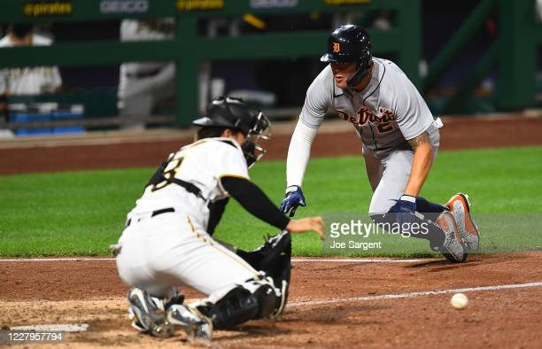 JaCoby Jones of the Detroit Tigers scores in front of John Ryan Murphy of the Pittsburgh Pirates during the tenth inning at PNC Park on August 7,...
