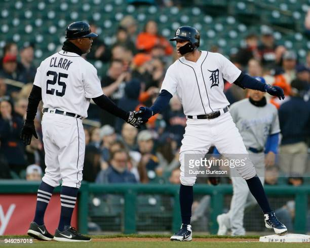 JaCoby Jones of the Detroit Tigers slaps hands with third base coach Dave Clark of the Detroit Tigers after hitting a standup double against the...